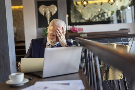 Senior businessman sitting at a restaurant table, working on a laptop computer, analyzing documentation and contract terms and conditions, angry and displeased