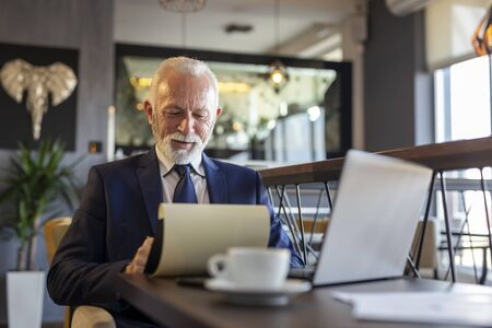 Senior businessman sitting at a restaurant table, working on a laptop computer, analyzing documentation and contracts and drinking coffee