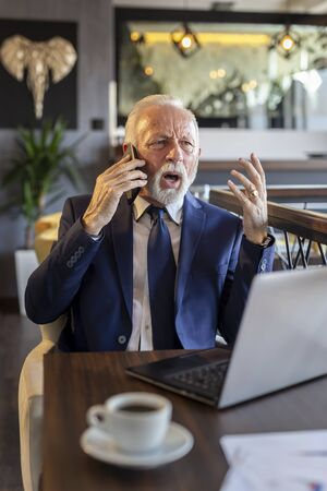 Senior businessman working in a modern office, having a phone conversation while working on a laptop computer, angry and displeased