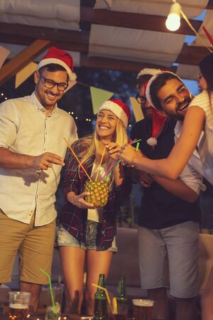Group of young friends wearing Santa hats, drinking pineapple cocktail at an outdoor New Years Eve party