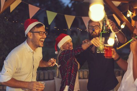 Group of friends having fun at an outdoor New Years Eve party, blowing party whilstes, dancing and drinking beer