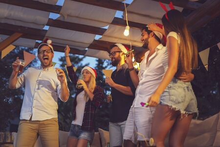 Group of young friends dancing, blowing party whistles, drinking and having fun at an outdoor New Years Eve party