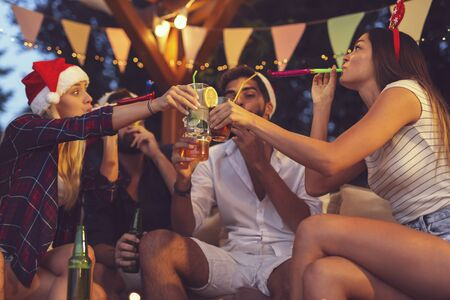 Group of young friends blowing party whistles, drinking beer, making a toast and having fun at an outdoor New Years Eve party