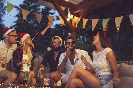 Group of young friends blowing party whistles, drinking beer and having fun at an outdoor New Years Eve party Imagens - 131936575