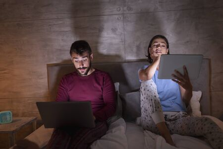 Beautiful young couple sitting side by side in bed at night, working late on laptop and tablet computers Imagens