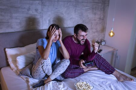 Beautiful young couple wearing pajamas, having fun at home, playing video games in bed at night, man excited after winning the game, woman disappointed after losing