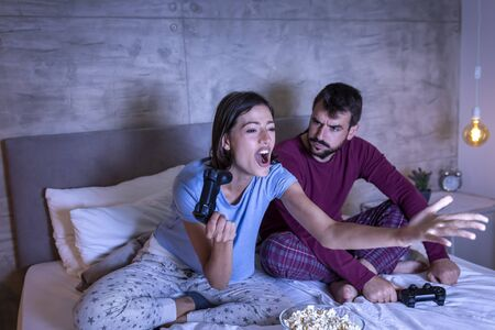 Beautiful young couple wearing pajamas, having fun at home, playing video games in bed at night, woman excited after winning the game, man disappointed after losing