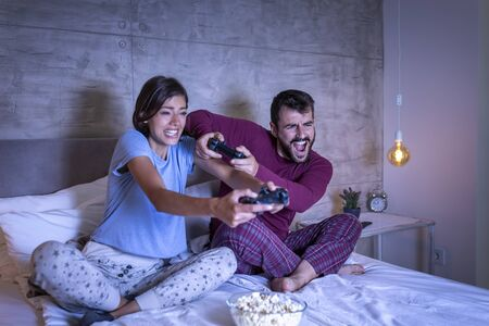 Beautiful young couple wearing pajamas, having fun at home, playing video games in bed at night