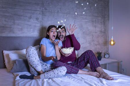 Beau jeune couple amoureux, assis dans son lit côte à côte, mangeant du pop-corn et s'amusant à regarder un film d'horreur la nuit