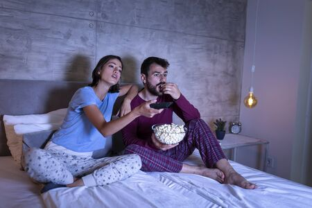 Beautiful young couple sitting in bed, wearing pajamas, eating popcorn and changing channels on TV, searching for a movie or TV show to watch