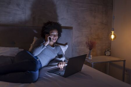 Beautiful young mixed race woman lying in bed at night, using a laptop computer and having a phone conversation Imagens