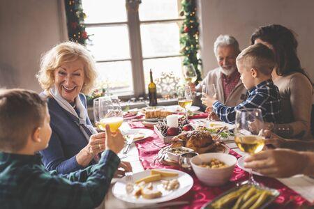 Gelukkige familie die Kerstmis viert, thuis eet, een toast uitbrengt met glazen wijn en sinaasappelsap en geniet van hun tijd samen