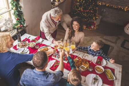High angle view of a beautiful happy family gathered around the table, having Christmas dinner all together at home, celebrating Christmas and making a toast