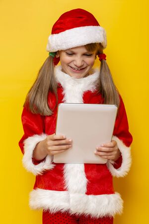 Beautiful little girl wearing Santa costume using a tablet computer, isolated on yellow colored background
