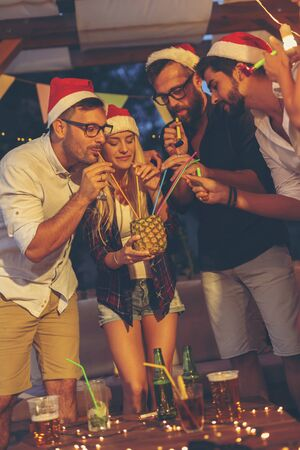 Group of friends wearing Santa hats, having fun while drinking pineapple cocktail at an outdoor New Years Eve party