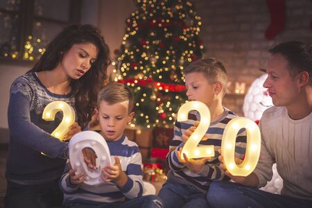 Rodzice świętujący Sylwestra w domu z dziećmi, siedzący przy choince, trzymający świecące cyfry 2020 reprezentujące nadchodzący Nowy Rok