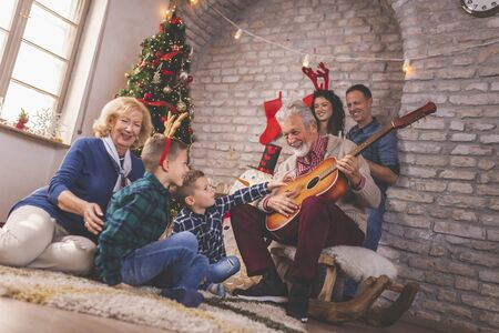 Beautiful happy family celebrating Christmas at home, gathered around Christmas tree, having fun while playing the guitar and singing Christmas songs