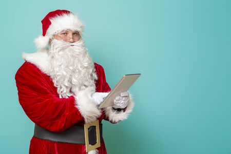 Portrait of Santa Claus using a tablet computer, isolated on mint colored background Stock Photo