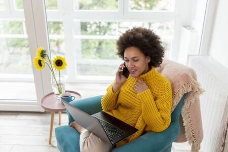 Beautiful mixed race woman sitting in an armchair, relaxing at home, using a laptop computer and speaking on the phone