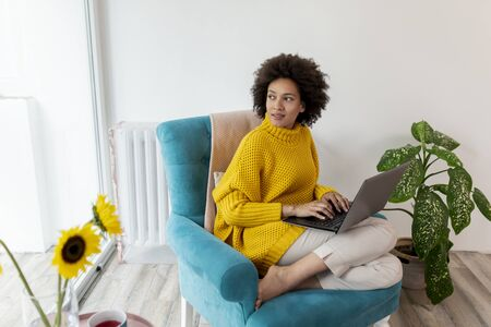 Beautiful mixed race woman sitting in an armchair, relaxing at home, using a laptop computer