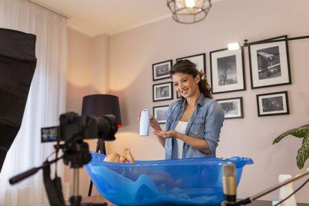 Female vloger recording video about newborn baby bathing as part of online prenatal classes; female influencer filming tutorial about newborn baby care Stock fotó