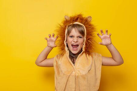 Hermosa niña vistiendo traje de carnaval de león rugiendo, aislado sobre fondo de color amarillo