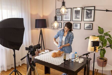 Influencer recording video about newborn baby care products; vlogger making tutorial about newborn baby care as part of online prenatal classes