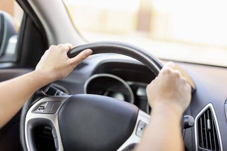 Dettaglio delle mani femminili che tengono un volante mentre guidano un'auto Archivio Fotografico