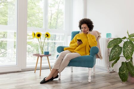 Beautiful mixed race woman sitting in an armchair, relaxing at home, typing a text message on a smartphone