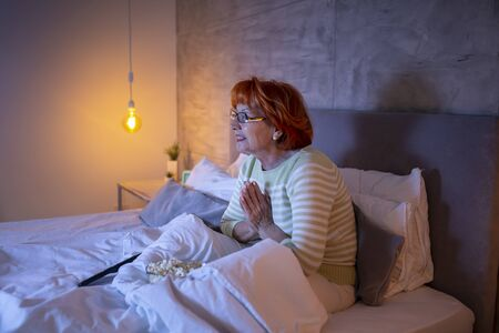 Senior woman wearing pajamas sitting on bed, eating popcorn, watching funny TV program and laughing