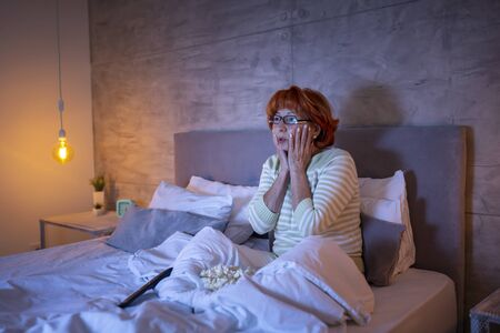 Beautiful senior woman wearing pajamas sitting on bed, eating popcorn and watching horror movie on TV, scared and tense