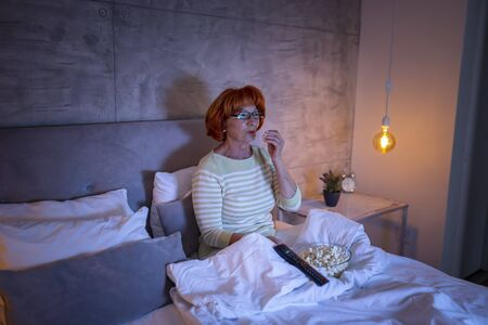 Senior woman wearing pajamas sitting on bed, eating popcorn, watching TV and relaxing at home at night Banque d'images - 137180037