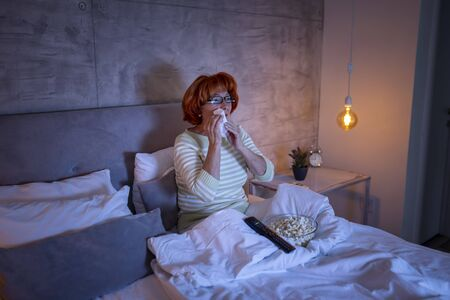 Senior woman wearing pajamas sitting on bed, watching drama movie on TV, sad, crying and wiping tears with a handkerchief Banque d'images - 137180038