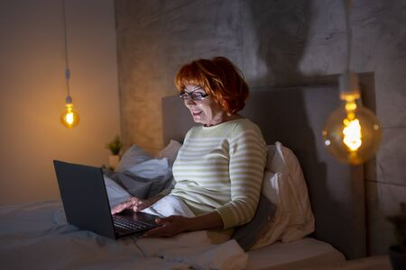 Beautiful senior woman lying in bed at night, having a video call on a laptop computer with family members