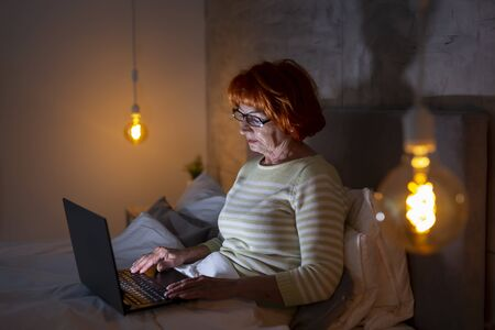 Beautiful senior woman wearing pajamas sitting in bed, typing an email on laptop computer; senior novelist writing a new book using laptop computer Banque d'images - 137180046