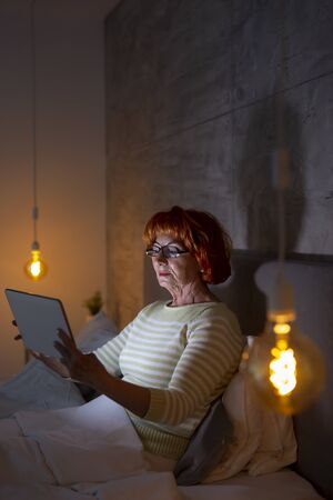 Beautiful senior woman wearing pajamas sitting in bed, surfing the net on tablet computer Standard-Bild