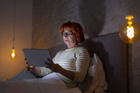 Beautiful senior woman wearing pajamas sitting in bed, reading an ebook on tablet computer Banque d'images - 137180050