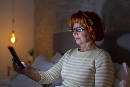 Senior woman wearing pajamas sitting on bed, having a video call with family members using a smart phone Imagens