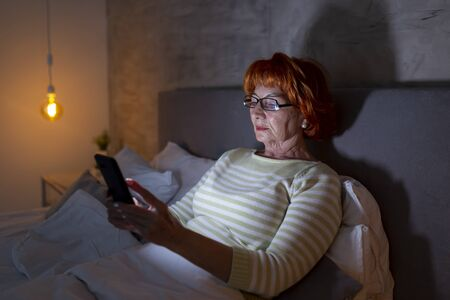 Senior woman wearing pajamas sitting on bed, using a smart phone Banque d'images - 137180056