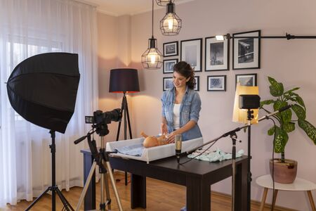 Female vlogger filming video about changing newborn baby nappies; female influencer making tutorial about newborn baby care as part of online prenatal classes