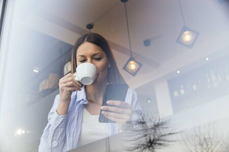 Portrait of a beautiful young woman sitting at a restaurant table, drinking coffee and typing a text message on a smart phone Banque d'images - 137180162