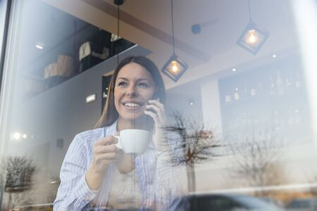 Portrait of a beautiful young woman sitting at a restaurant table, looking out the window, drinking coffee and speaking on the phone Banque d'images - 137180165