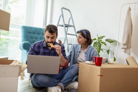 Beautiful young couple in love moving in together, sitting among cardboard boxes in their new apartment, having breakfast and searching for redecoration ideas Stockfoto