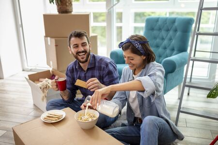 Beautiful young couple in love moving in together, sitting among cardboard boxes in their new apartment, having fun while eating breakfast Stockfoto