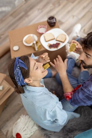 Top view of young couple in love sitting on the floor among cardboard boxes, having fun while eating breakfast in their new apartment