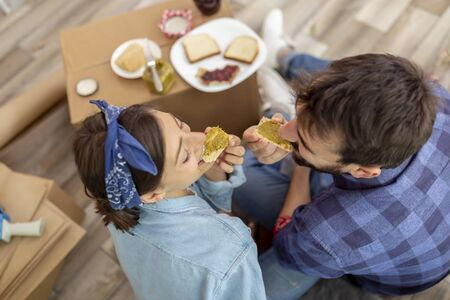 Top view of young couple in love sitting on the floor among cardboard boxes, having fun while eating breakfast in their new apartment. Focus on woman's sandwich Stockfoto - 137671555