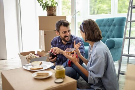 Couple in love moving in together, taking a break from unpacking cardboard boxes, having fun while eating breakfast Stockfoto - 137671557