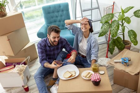 Couple in love moving in together, taking a break from unpacking cardboard boxes, having fun while eating breakfast