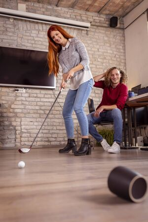 Business colleagues having fun at the office, playing mini golf; freelancers working in coworking space, taking a break and having fun playing mini golf Stockfoto - 137764542