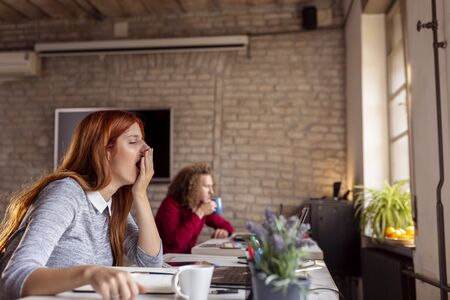 Business people working in a modern office; freelancers working in a coworking space, woman yawning while sitting at her office desk Stockfoto